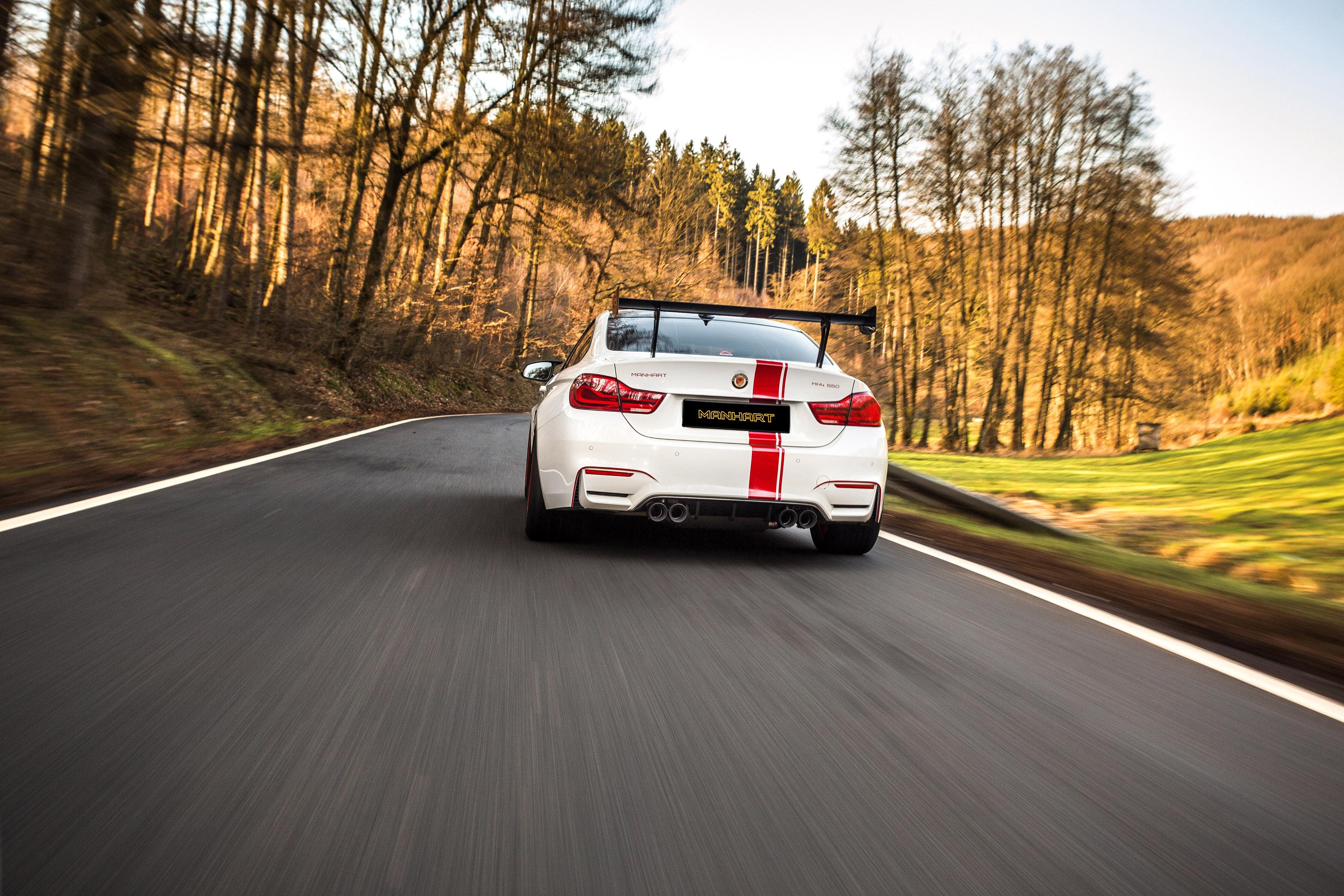 Белый кузов элегантно дополнен ярко-красными полосками и красными колесными дисками M-Performance. Кроме того, передний спойлер и задний диффузор выполнены из глянцевого карбона. Также Manhart установил массивный задний спойлер из карбона и острые эл